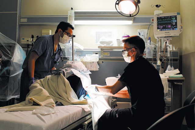 Dr. J.D. McCourt, right, tends to a patient at University Medical Center, where he is medical director of the hospital's Adult Emergency Department. Diagnosis of a kidney stone can take one to two ...