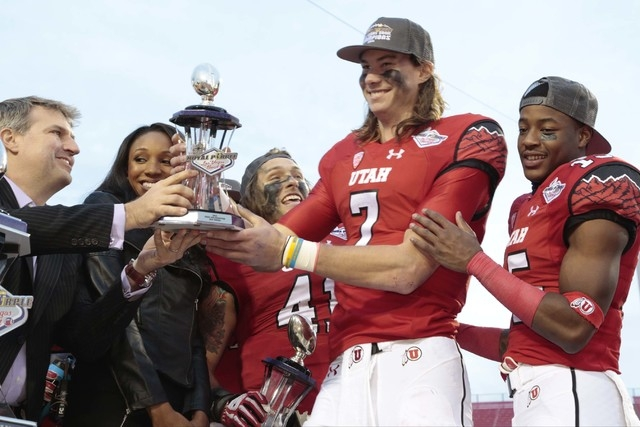 University of Utah's Travis Wilson (7)(QB) is presented the MVP trophy by Royal Purple , President Bryan Yurdon -left ,  and supported by fellow team mate University of Utah's Dominique Hatfield ( ...