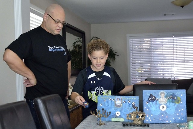 Damon Sims, left, watches as his son Cole helps unpack some Hanukkah-related holiday decorations at their home near West Lake Mead Boulevard and Harbor Island Drive in Las Vegas on Saturday, Dec.  ...