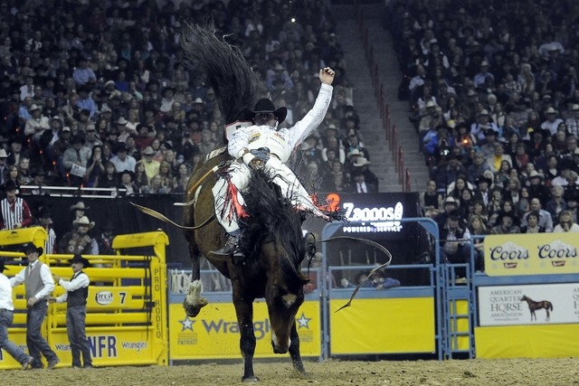 Bareback rider Kaycee Feild from Spanish Fork, Utah, rides Pete Carr's Classic Pro Rodeo's Scarlet's Web to a second place score of 86 during the tenth go-round of the National Finals Rodeo at the ...