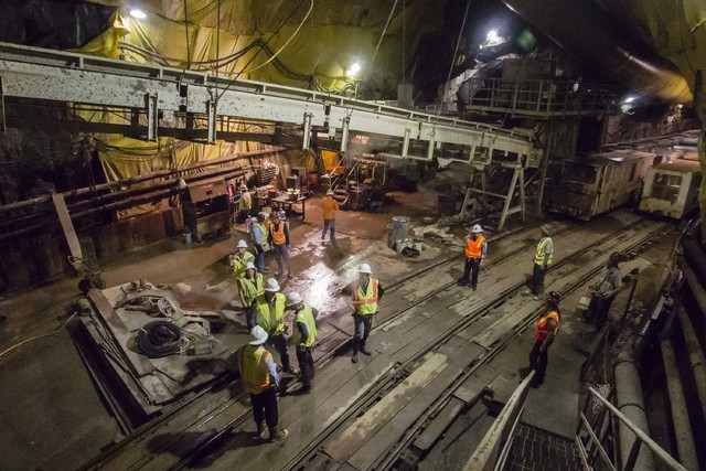 Workers and tour members gather at a staging area 600 feet below the surface where a train will take them 3 miles to the drill bore machine on Tuesday Sept. 16, 2014.  Intake No. 3, as it is offic ...