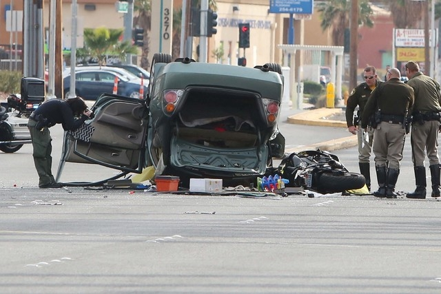 A Las Vegas police accident scene photographer, left, takes a picture at the accident scene where two people died on the 3100 block of Valley View Blvd., on Saturday, Dec. 20, 2014.  (Bizuayehu Te ...
