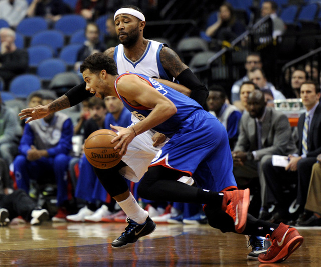 Philadelphia 76ers guard Michael Carter-Williams, in blue, drives against Minnesota Timberwolves guard Mo Williams during the first quarter of an NBA basketball game Wednesday, Dec. 3, 2014, in Mi ...