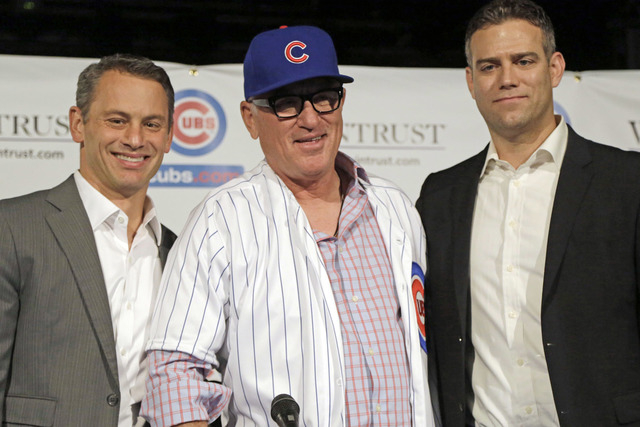 Chicago Cubs general manager Jed Hoyer, left, and president of baseball operations Theo Epstein stand with Joe Maddon as he is introduced as the new manager of the Cubs baseball team Monday, Nov.  ...