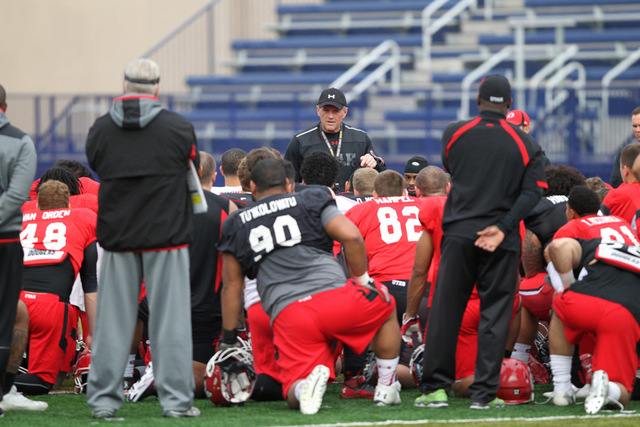 Utah Utes head coach Kyle Whittingham, center, talks to his players following a team practice at Fertitta Field inside Bishop Gorman Catholic High School in Las Vegas Wednesday, Dec. 17, 2014. Uta ...