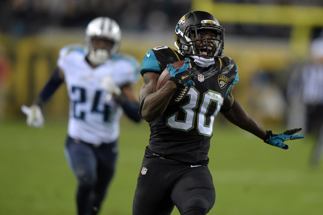 Jacksonville Jaguars running back Jordan Todman (30) is pursued by Tennessee Titans cornerback Coty Sensabaugh (24) on a 62-yard touchdown run in the fourth quarter at EverBank Field. The Jaguars  ...