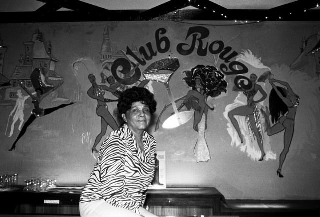 """Portrait of the operator of the Moulin Rouge Sarann Knight Preddy sitting in front of a mural with buildings and dancers and """"Club Rouge"""" on the wall. Preddy and her husband Joe lease th ..."""