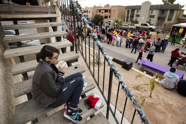 Constance Pacheco, 16, sips hot chocolate on a stairwell of her parents apartment during a community block party Friday, Dec. 19, 2014 at the Sierra Oeste community in northwest Las Vegas. One yea ...