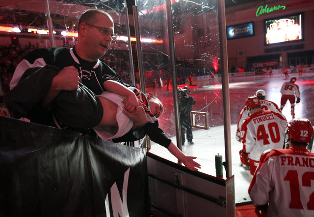 Brian Isaacson holds his son Andrew up to give him better reach to give Wranglers hockey players a high-five as they enter the Orleans Arena in Las Vegas Saturday, Jan. 4, 2014.  (John Locher/Las  ...