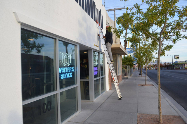 A painter works on the sign outside The Writer's Block on the stores preview opening day Nov. 29. (Ginger Meurer/View)