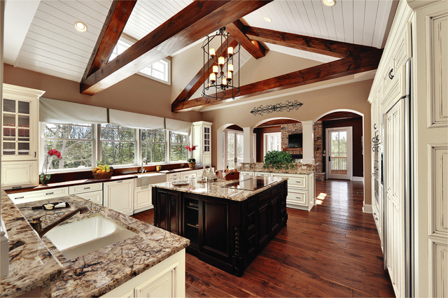 Family Features The architectural and top-to-bottom details are crucial to the design of this traditional kitchen. From the beams and archways to the mullion cabinet doors and island legs, this ki ...