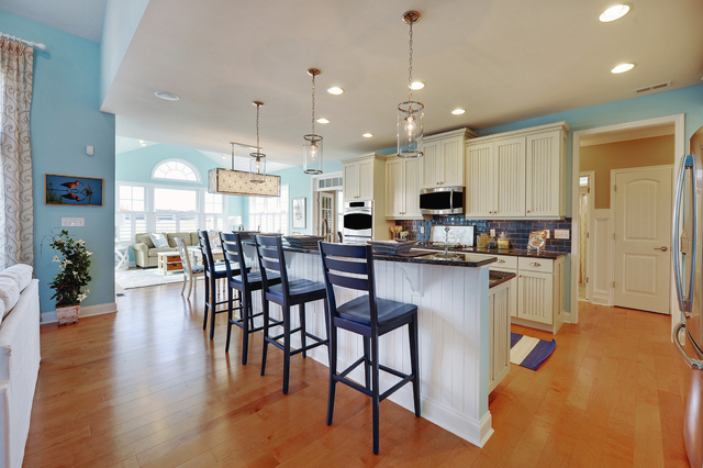 Family Features The combination of the bead board panel from the cabinets and wall paint color gives this casual kitchen a coastal feel. This causal design makes for a comfortable environment.