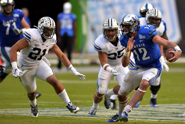 Dec 22, 2014; Miami, FL, USA; Memphis Tigers quarterback Paxton Lynch (12) scrambles away from Brigham Young Cougars running back Jamaal Williams (21) during the third quarter in the Miami Beach B ...
