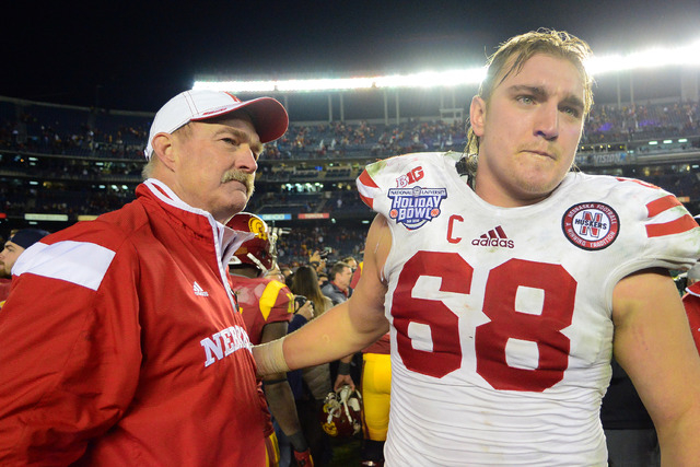 Nebraska Cornhuskers head coach Barney Cotton (left) looks on as offensive lineman Jake Cotton (68) walks off the field after the 2014 Holiday Bowl at Qualcomm Stadium. Cotton is UNLV's new offens ...