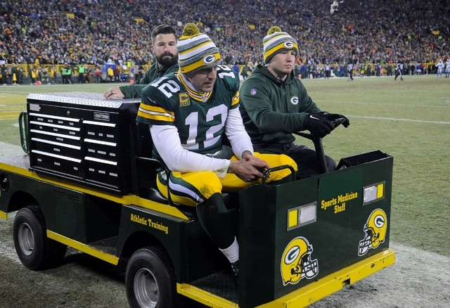 Dec 28, 2014; Green Bay, WI, USA;  Green Bay Packers quarterback Aaron Rodgers (12) is taken off the field on a cart after an injury in the second quarter during the game against the Detroit Lions ...
