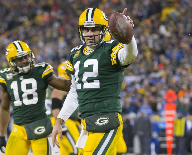 Dec 28, 2014; Green Bay, WI, USA; Green Bay Packers quarterback Aaron Rodgers (12) celebrates after scoring a touchdown during the fourth quarter against the Detroit Lions at Lambeau Field.  Green ...