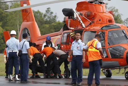 The body of an AirAsia QZ8501 passenger, recovered from the Java Sea, is placed on a stretcher after it was transported by an Indonesia Search and Rescue helicopter at an airbase Pangkalan Bun, Ce ...