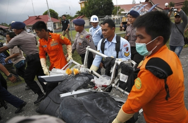 Parts of AirAsia QZ8501, recovered from the Java Sea, are carried by Indonesian Airforce and Search and Rescue crew after they were offloaded from a U.S. Navy helicopter at the airport in Pangkala ...