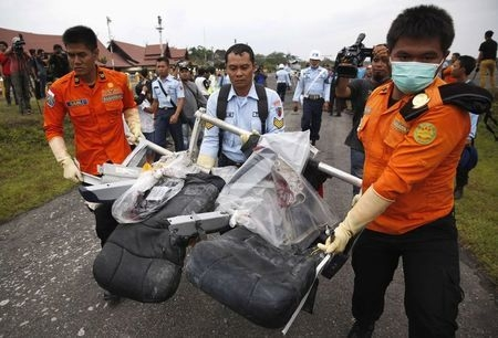 Parts of AirAsia QZ8501, recovered from the Java Sea, are carried by Indonesian Airforce and Search and Rescue crew members after they were offloaded from a U.S. Navy helicopter at the airport in  ...
