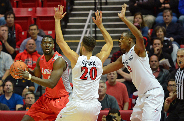 Jan 6, 2015; San Diego, CA, USA; New Mexico Lobos center J.J. N'Ganga (left) is defended by San Diego State Aztecs forward J.J. O'Brien (20) and forward Skylar Spencer (0) during the first half at ...