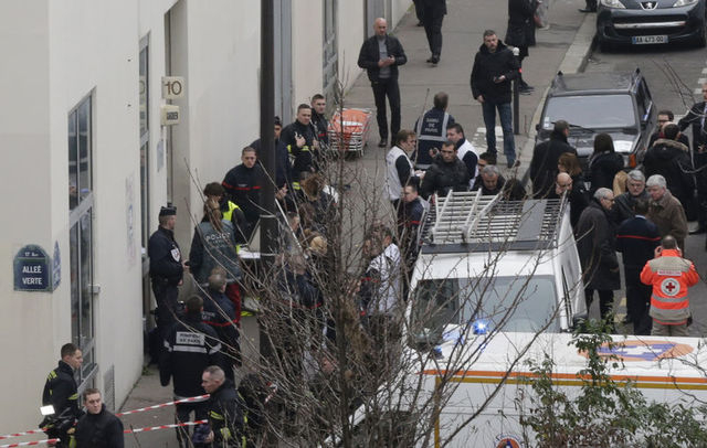 Firefighters and rescue members stand in front of the Paris offices of Charlie Hebdo, a satirical newspaper, after a shooting on Wednesday, Jan. 7, 2015. (Reuters/Philippe Wojazer)