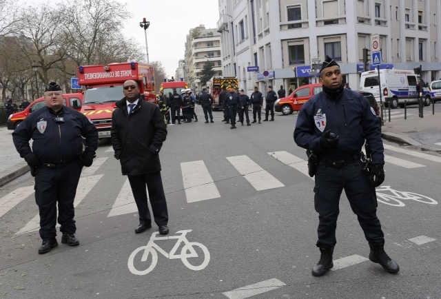 Policemen work at the scene after a shooting at the Paris offices of Charlie Hebdo, Wednesday, Jan. 7, 2015. Hooded gunmen stormed the Paris offices of the weekly satirical magazine known for lamp ...