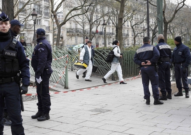 Policemen work at the scene after a shooting at the Paris offices of Charlie Hebdo, Wednesday, January 7, 2015. Hooded gunmen stormed the Paris offices of the weekly satirical magazine known for l ...