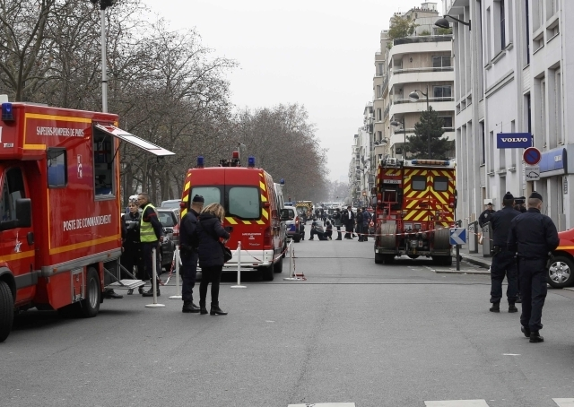 Policemen work at the scene after a shooting at the Paris offices of Charlie Hebdo January 7, 2015. Hooded gunmen stormed the Paris offices of the weekly satirical magazine known for lampooning ra ...