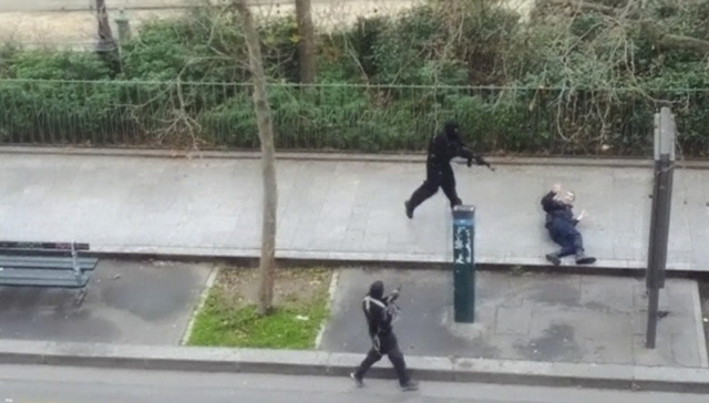 Gunmen flee after shooting a wounded police officer, right, on the ground at point-blank range outside the offices of French satirical newspaper Charlie Hebdo in Paris, in this still image taken f ...
