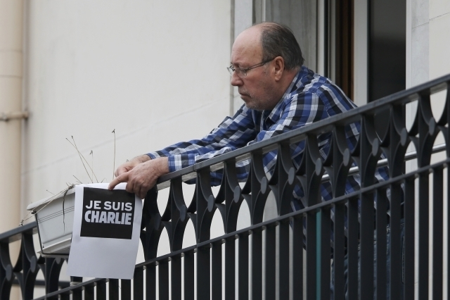 """A resident holds a placard which reads """"I am Charlie"""" on a balcony near the scene after a shooting at the Paris offices of Charlie Hebdo, Wednesday, Jan. 7, 2015. Gunmen stormed the Paris offices  ..."""