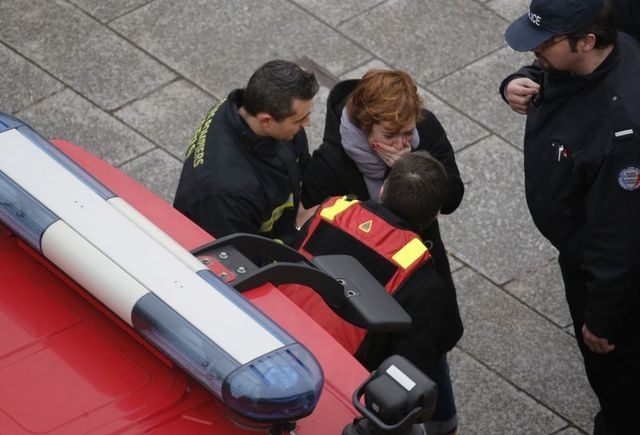 A distressed woman is assisted  by firemen near the scene after a shooting at the Paris offices of Charlie Hebdo, a satirical newspaper, Wednesday, Jan. 7, 2015.   (Reuters/Christian Hartmann)