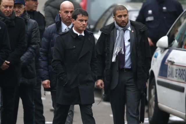 French Prime Minister Manuel Valls, center, stands near the Paris offices of Charlie Hebdo, Wednesday, Jan. 7, 2015 after a shooting. (Reuters/Charles Platiau)