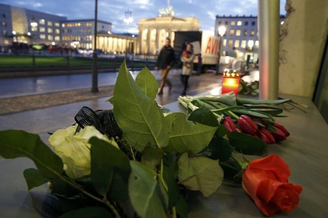 People walk past flowers of condolance placed at the French embassy at Pariser Platz in Berlin, Wednesday, Jan. 7, 2015. (Reuters/Fabrizio Bensch)