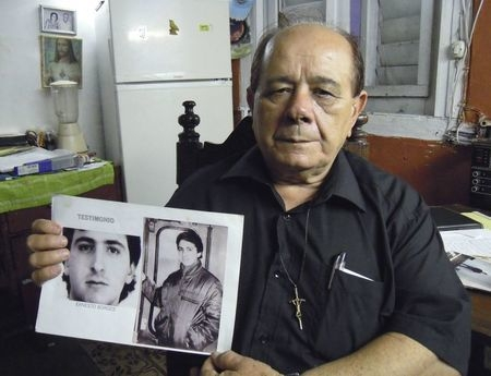 Raul Borges, 74, holds a picture of his son Ernesto Borges in his house in Havana, Jan. 2, 2015. (Reuters/David Adams)