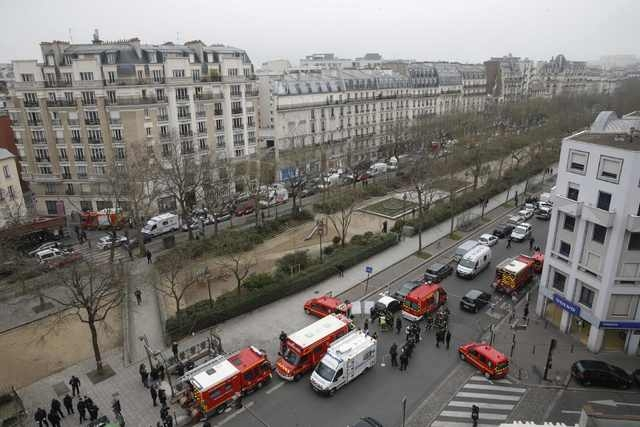 Police and rescue forces are seen near the scene after a shooting at the Paris offices of Charlie Hebdo, a satirical newspaper, Wednesday, Jan. 7, 2015. Gunmen stormed the Paris offices of the wee ...