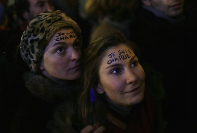 """Women with """"I am Charlie"""" written on their foreheads attend a vigil to pay tribute to the victims of a shooting by gunmen at the offices of weekly satirical magazine Charlie Hebdo in Paris at Repu ..."""