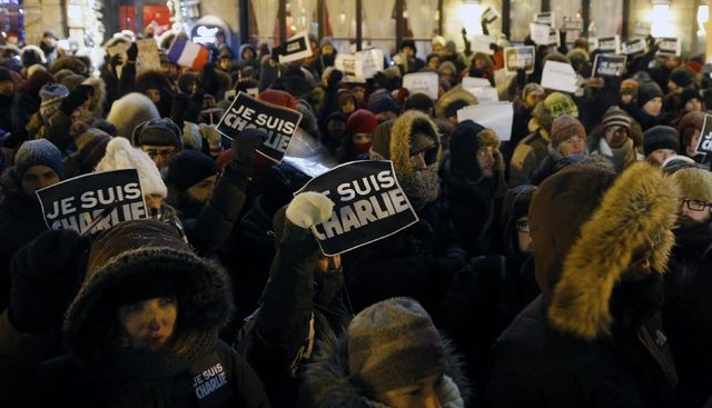 People hold signs during a vigil, for the victims of a shooting by gunmen at the offices of weekly satirical magazine Charlie Hebdo in Paris, at the French consulate in Quebec City, January 7, 201 ...