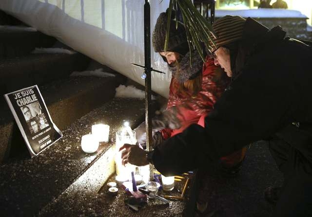 People light candles during a vigil, for the victims of a shooting by gunmen at the offices of weekly satirical magazine Charlie Hebdo in Paris, at the French consulate in Quebec City, January 7,  ...