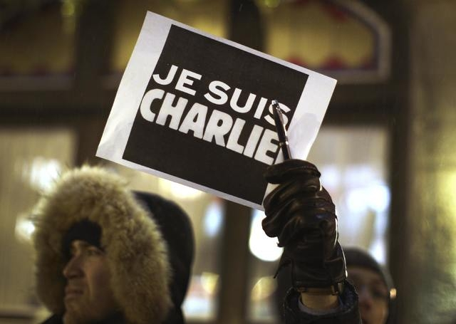 A man holds a pen with a sign during a vigil, for the victims of a shooting by gunmen at the offices of weekly satirical magazine Charlie Hebdo in Paris, at the French consulate in Quebec City, Ja ...