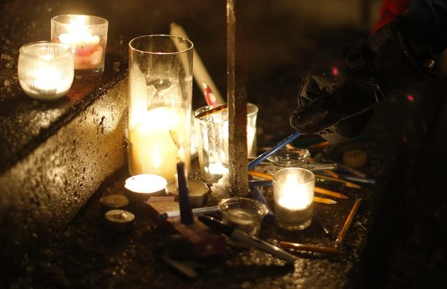 A man leaves a pen during a vigil, for the victims of a shooting by gunmen at the offices of weekly satirical magazine Charlie Hebdo in Paris, at the French consulate in Quebec City, January 7, 20 ...