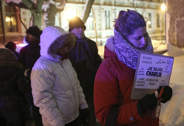 People wait in line to pay their respects during a vigil,  for the victims of a shooting by gunmen at the offices of weekly satirical magazine Charlie Hebdo in Paris, during a vigil at the French  ...