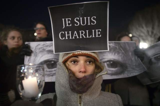 Amandine Marbach from Strasbourg, France, takes part in a vigil to pay tribute to the victims of a shooting, by gunmen at the offices of weekly satirical magazine Charlie Hebdo in Paris, in the Ma ...