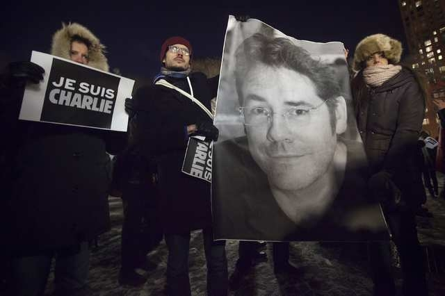People hold a poster of Bernard Verlhac, a cartoonist known as Tignous, who was killed by gunmen at the offices of weekly satirical magazine Charlie Hebdo in Paris, during a vigil to pay tribute t ...