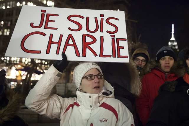 """A woman holds a sign reading """"I am Charlie"""" during a vigil to pay tribute to the victims of a shooting, by gunmen at the offices of weekly satirical magazine Charlie Hebdo in Paris, in the Manhatt ..."""