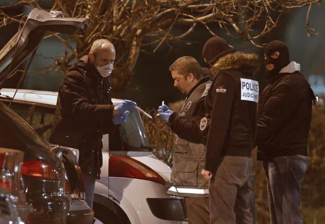 Police investigators search for evidence during an operation in the eastern French city of Reims, Thursday, Jan. 8, 2015, after the shooting against the Paris offices of Charlie Hebdo, a satirical ...
