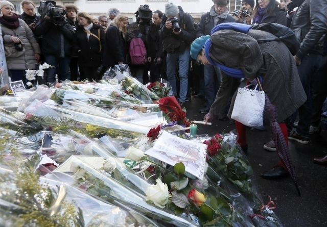 A woman lights a candle as journalists and citizens surround flowers placed in front of the offices of weekly satirical newspaper Charlie Hebdo in Paris, Thursday, Jan. 8, 2015, the day after a sh ...