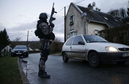 A member of the French GIPN intervention police forces secures a neighbourhood in Corcy, northeast of Paris, Thursday, Jan. 8, 2015. (Reuters/Christian Hartmann )