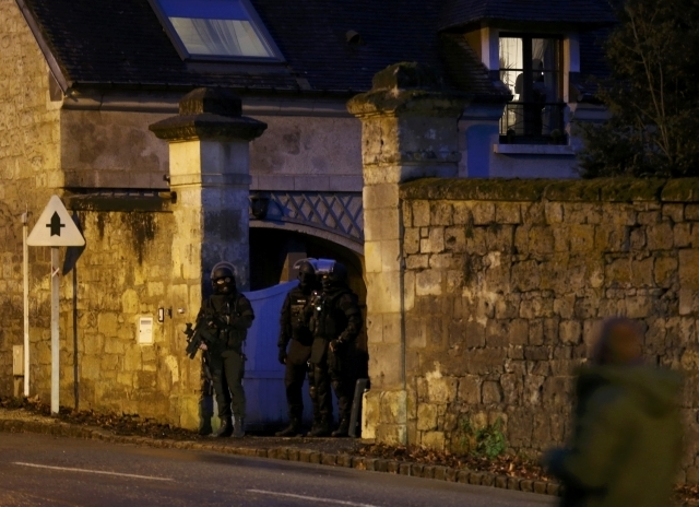 Members of the French GIPN intervention police forces secure a neighborhood in Corcy, northeast of Paris, Thursday, Jan. 8, 2015. French anti-terrorism police converged on an area northeast of Par ...