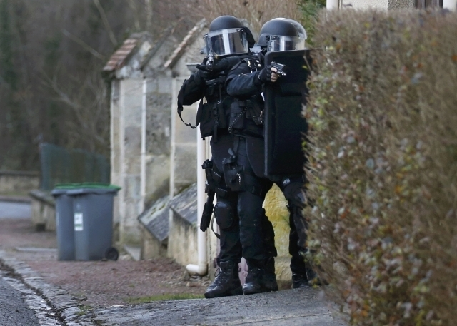 Members of the French GIPN intervention police forces secure a neighborhood in Longpont, northeast of Paris, Thursday, Jan. 8, 2015. French anti-terrorism police converged on an area northeast of  ...
