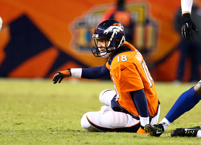 Jan 11, 2015; Denver, CO, USA; Denver Broncos quarterback Peyton Manning reacts as he sits on the ground after being sacked in the second half against the Indianapolis Colts in the 2014 AFC Divisi ...